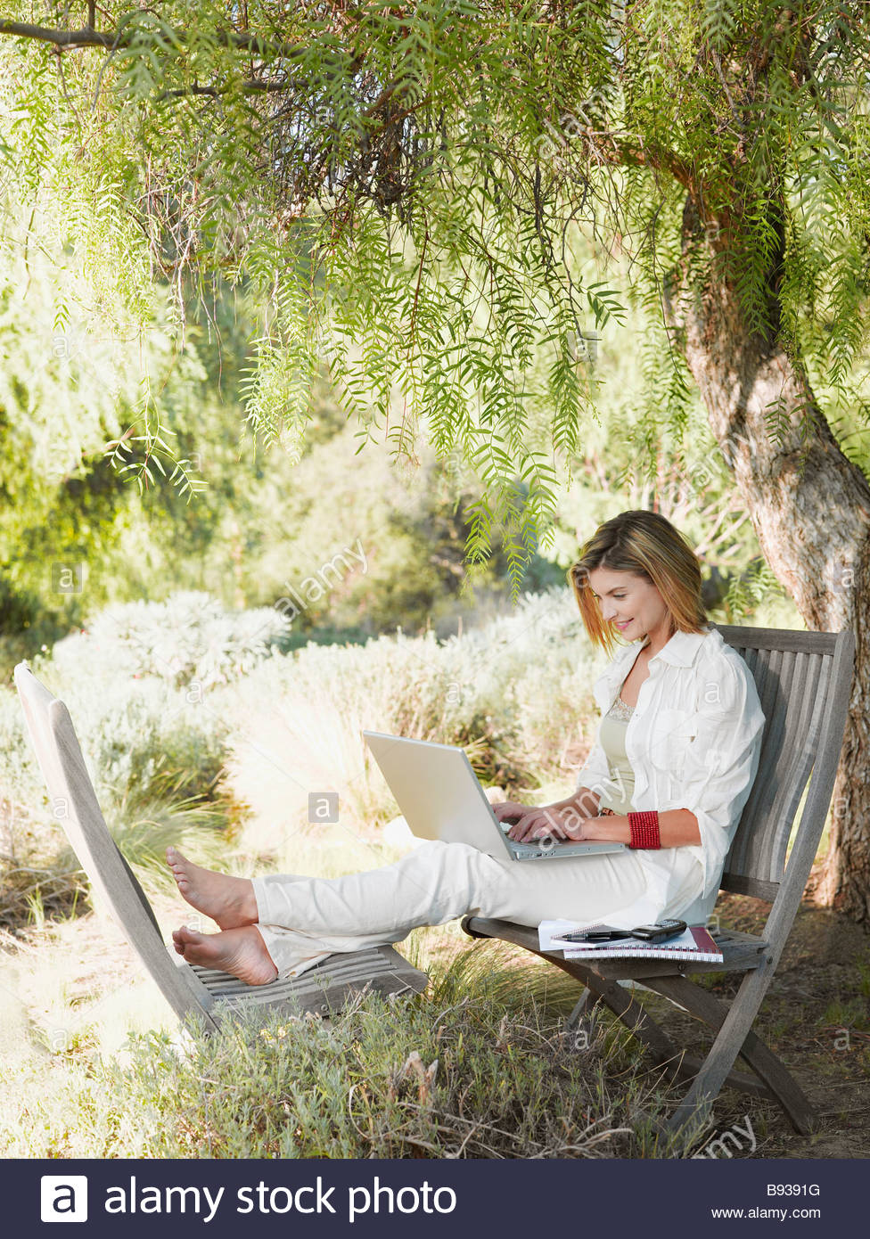 Woman using laptop in garden - Stock Image
