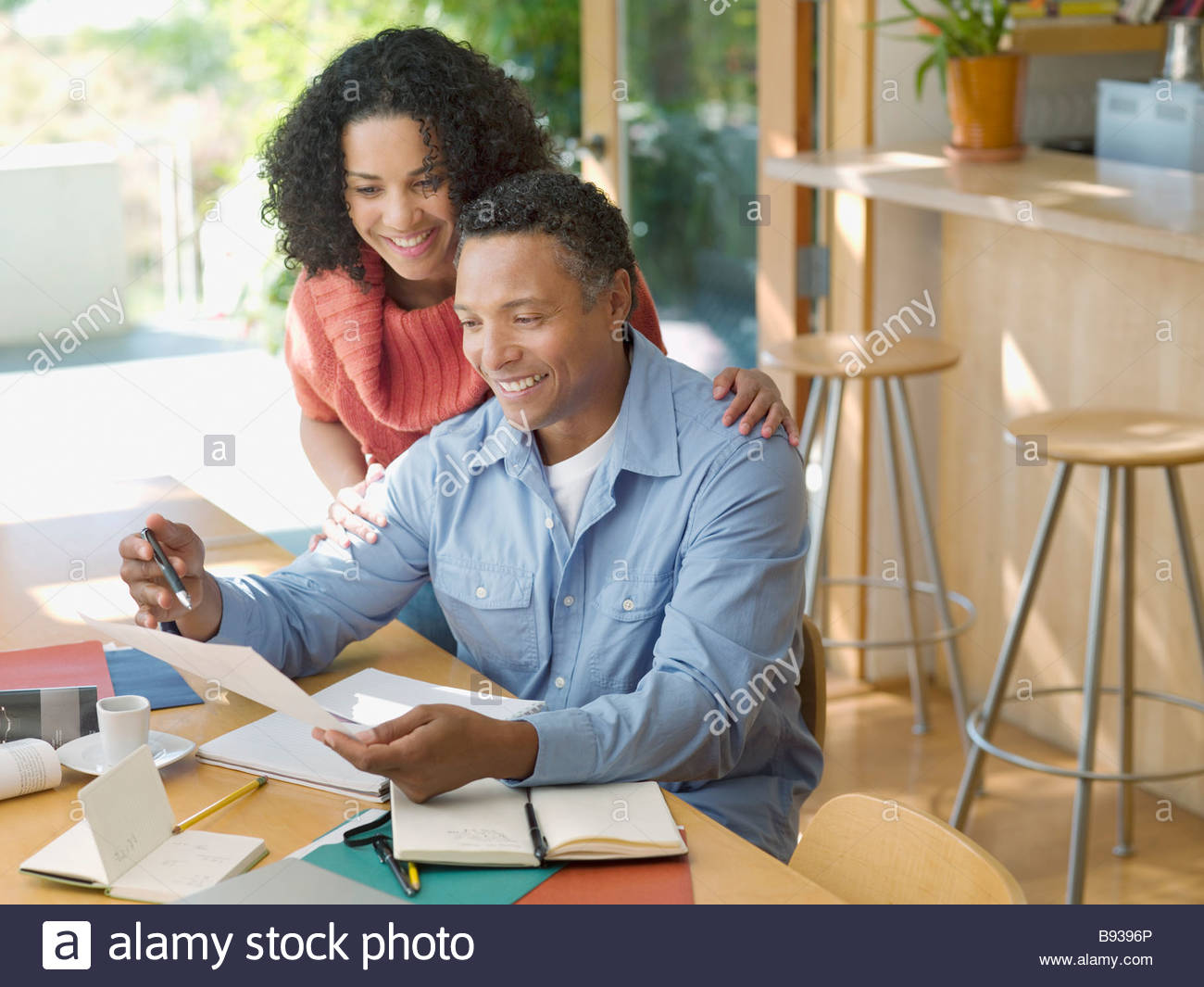 Couple reviewing paperwork at home - Stock Image