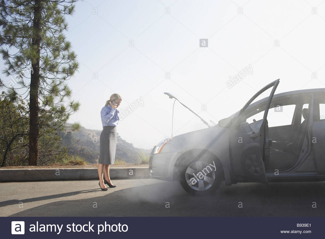 Woman calling for roadside assistance - Stock Image