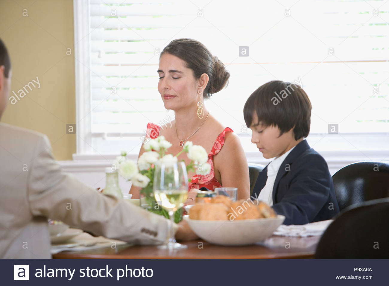 Family saying grace before dinner - Stock Image