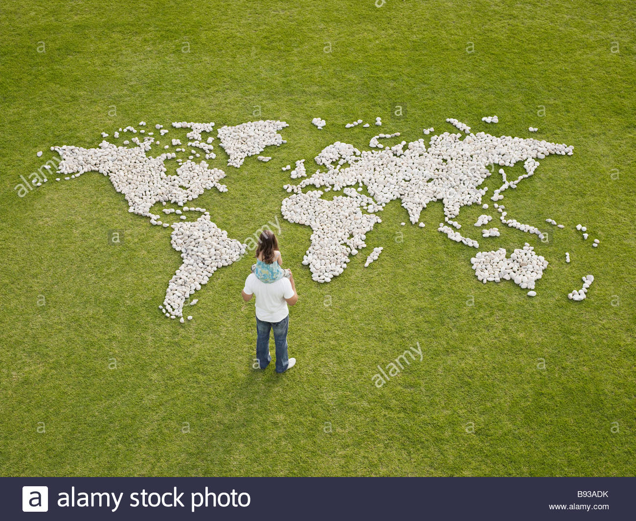 Father and daughter looking at world map made of rocks - Stock Image