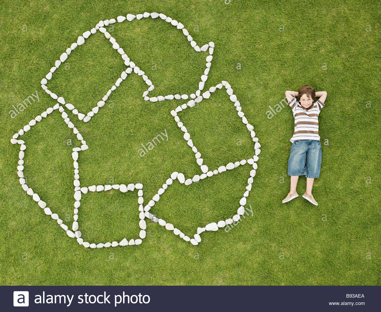 Boy relaxing near recycling symbol made of rocks - Stock Image
