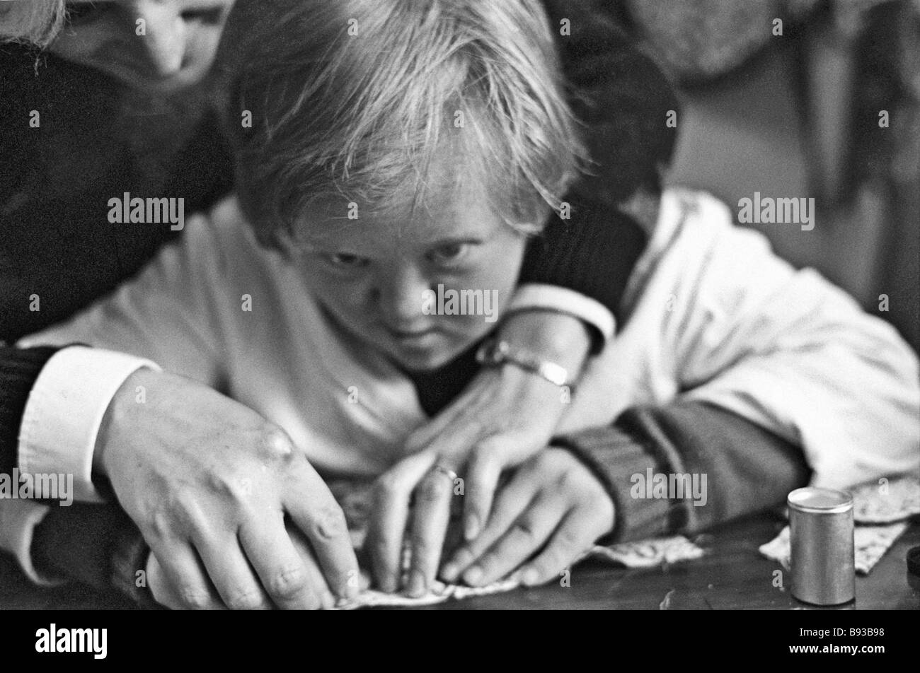 Moscow school No 486 pupil learning to sew at a special workshop opened at the initiative of the Moscow Down Syndrome - Stock Image
