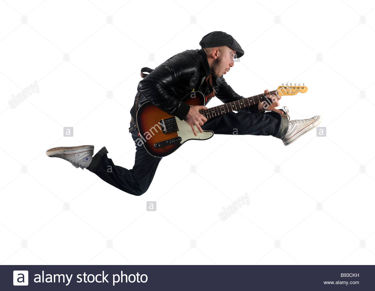 A band member jumps whilst holding a guitar - Stock Image
