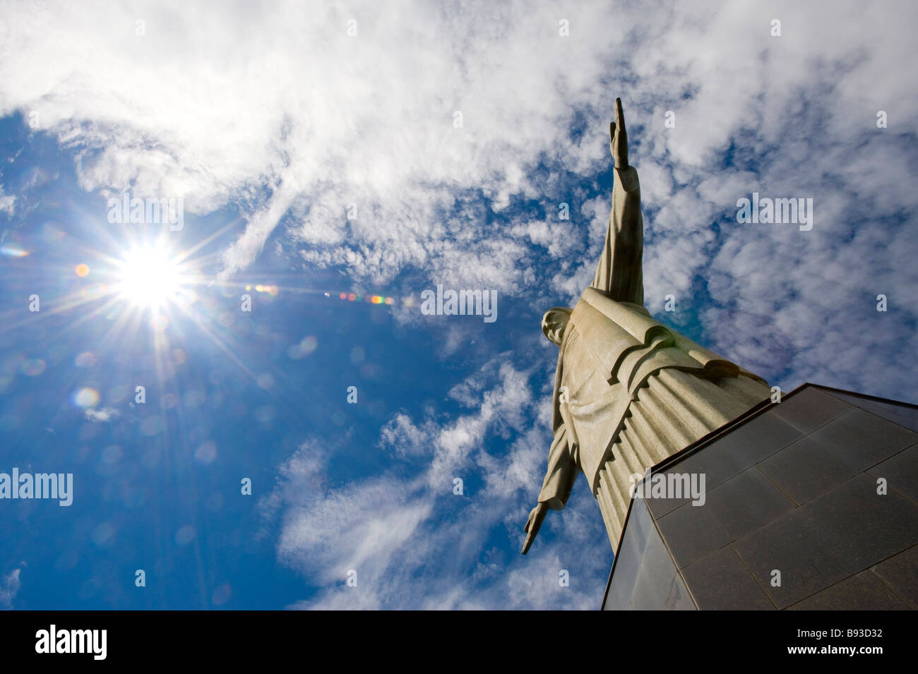 CHRIST THE REDEEMER STATUE ON CORCOVADO HILL RIO DE JANEIRO AS SUNLIGHT FLARES ON OUTSTRETCHED ARMS Stock Photo
