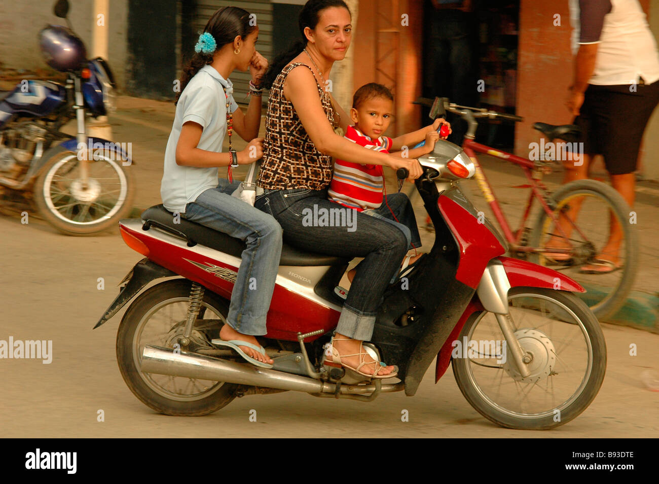 Moped scooter mother two child safety driving unsafely family colour metropolitan urban viajar outdoors transport - Stock Image