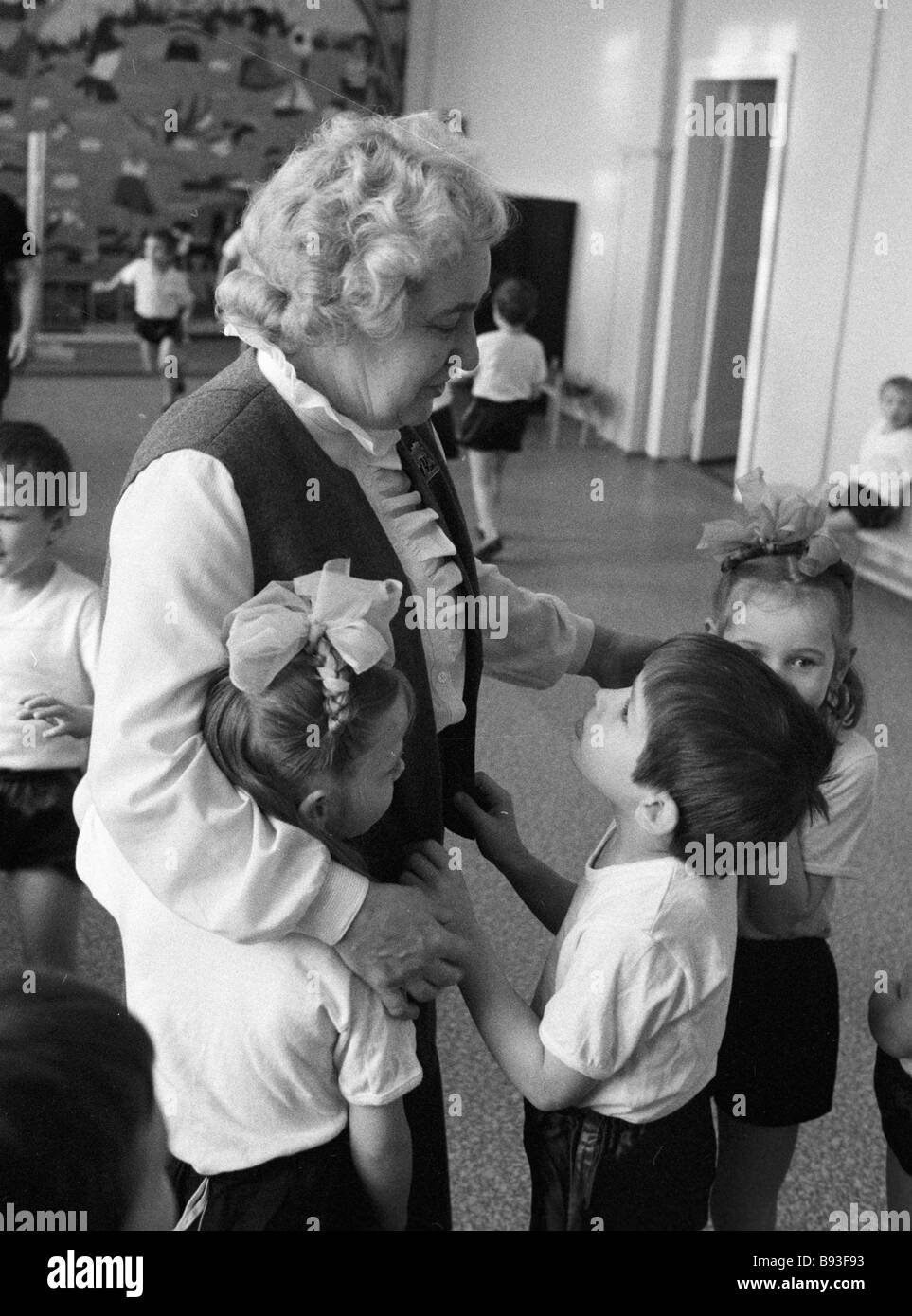 Instructor talks to children at orphanage No 29 - Stock Image