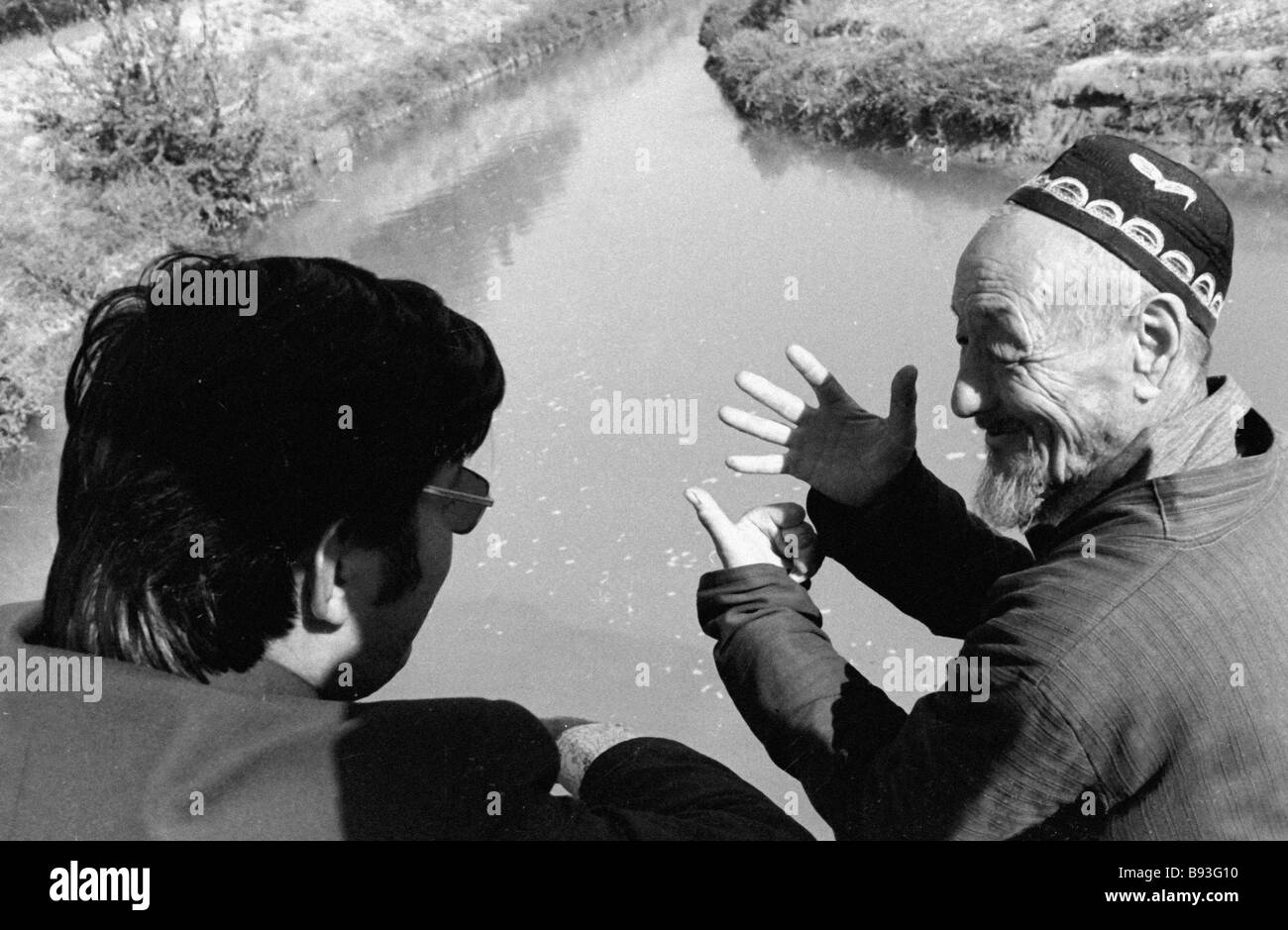 An elderly Kyrgyz man showing the irrigation canal in the construction of which he took part in the 1930s - Stock Image