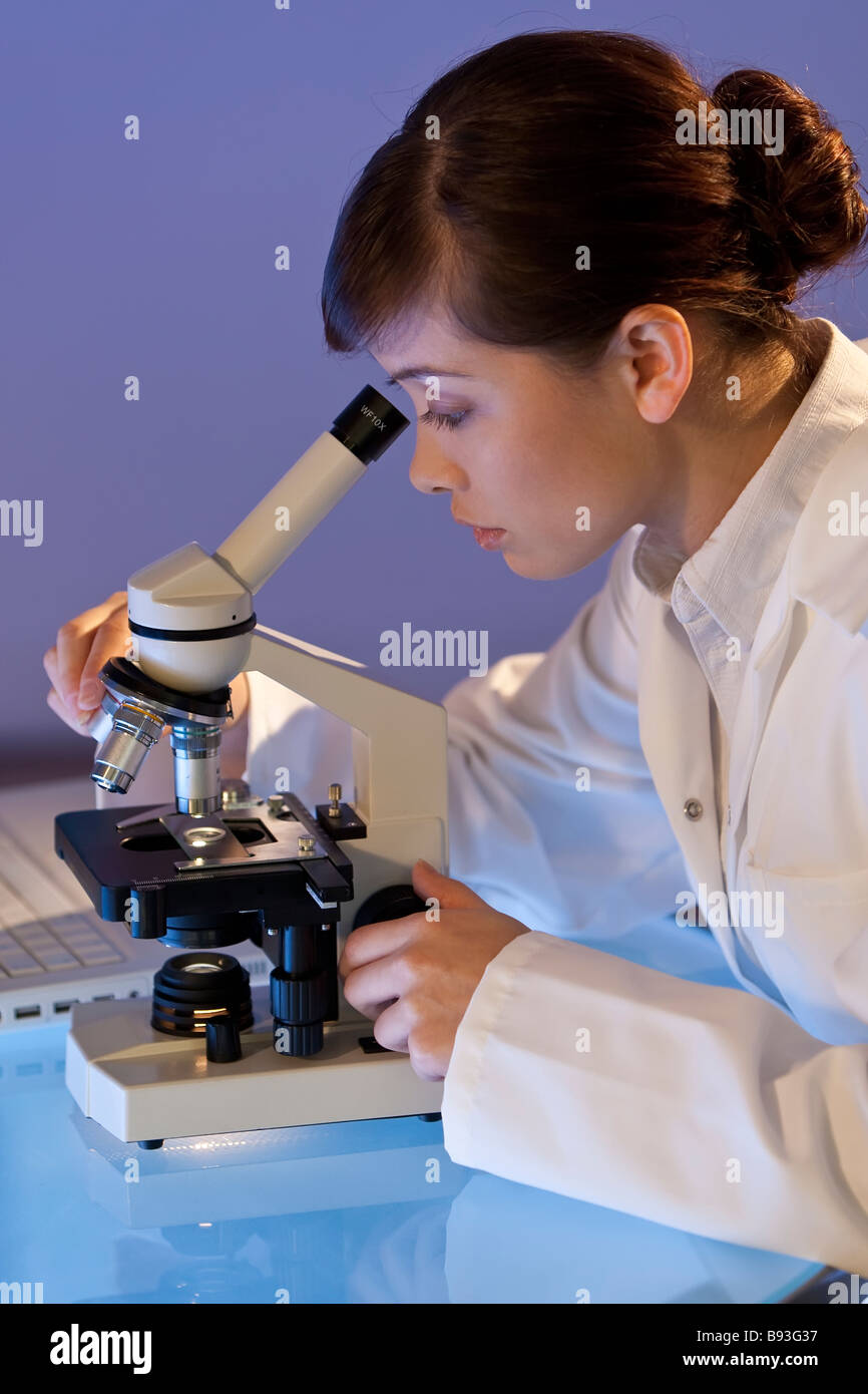 A beautiful female medical or scientific researcher using her microscope - Stock Image