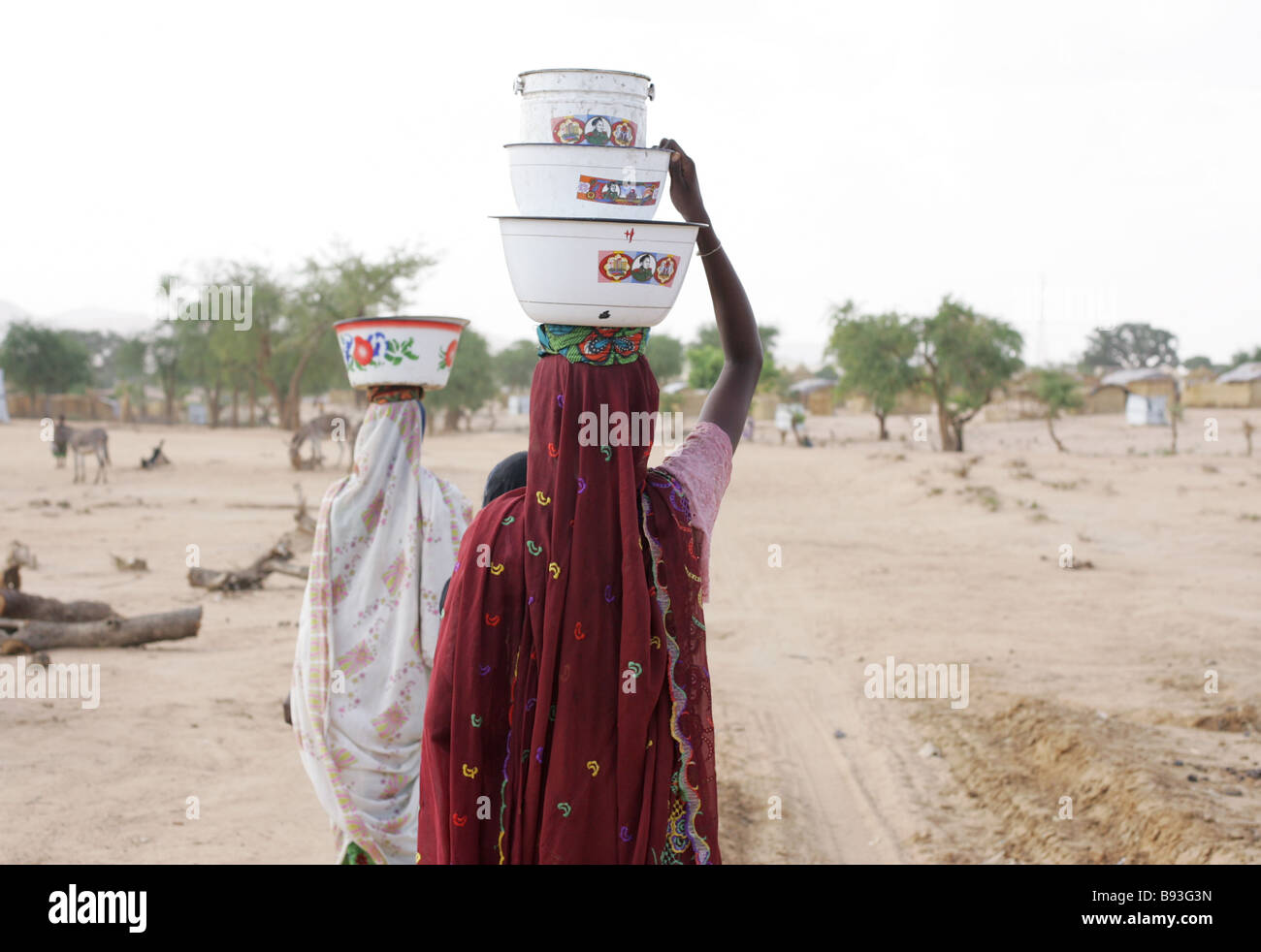 Women carry water in an internally displaced persons (IDP) camp in Goz Beida, Eastern Chad, Africa - Stock Image