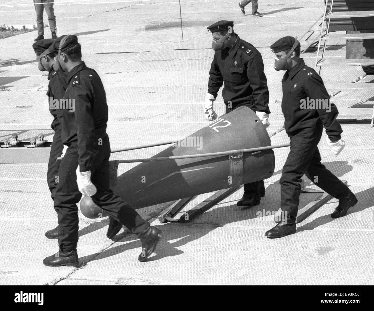 Technicians carry the warhead of RSD 10 rocket removed from combat duty - Stock Image