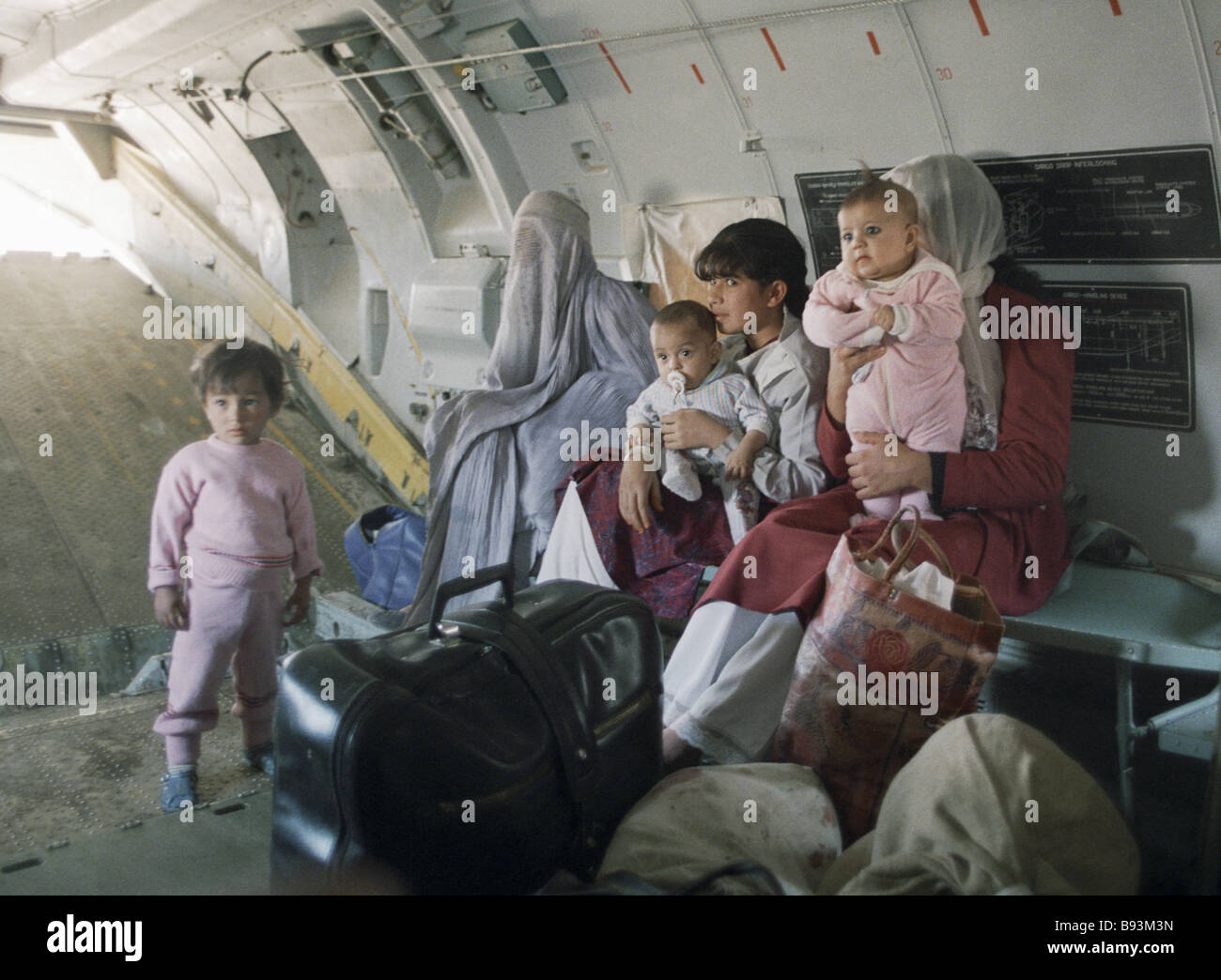 Afghan women with children in a military transport aircraft - Stock Image