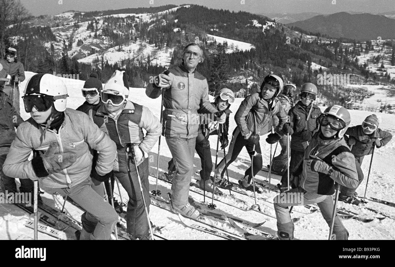 The coach of the Dynamo youth specialized sport school with his pupils at downhill skiing lessons - Stock Image