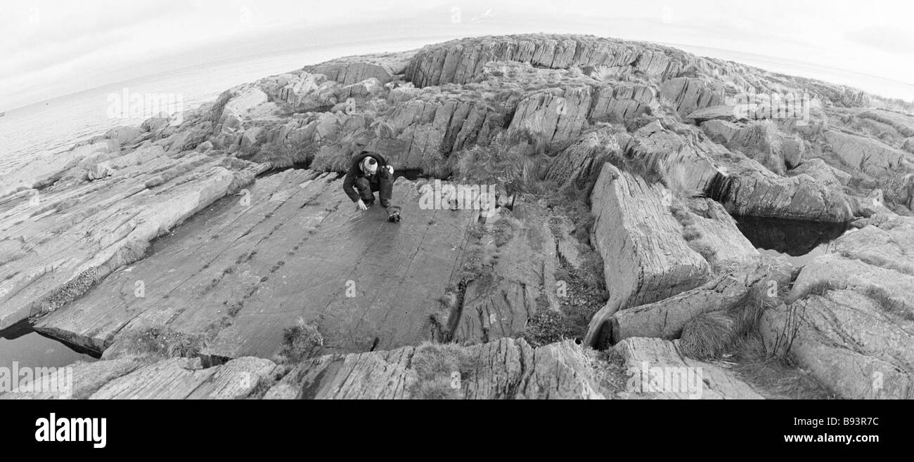A tourist looking at a rectangular shale plate in the center of Anikiev Island in Barents Sea stone annals of seafaring - Stock Image