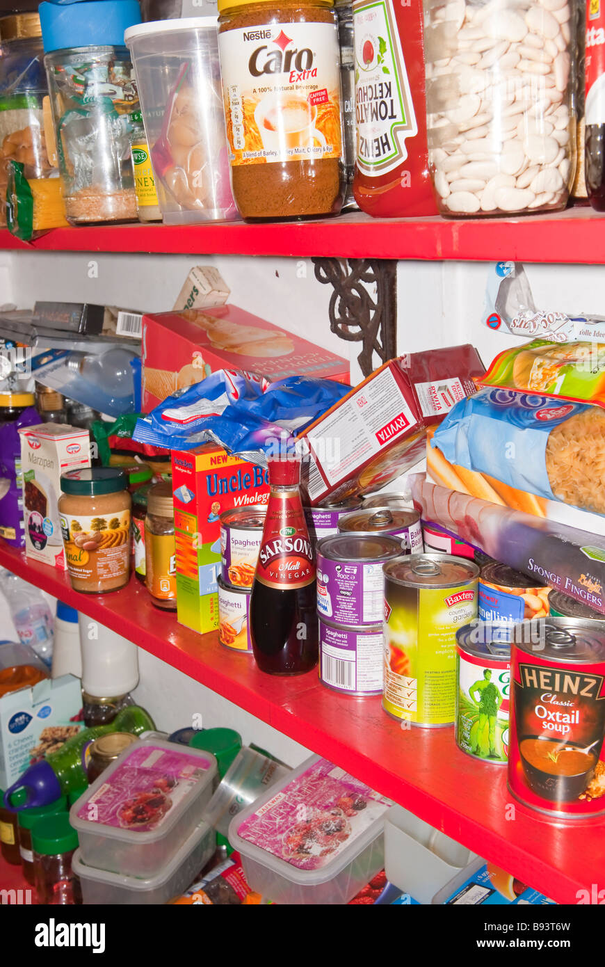 A cluttered untidy larder pantry housing lots of jars and tins etc. - Stock Image