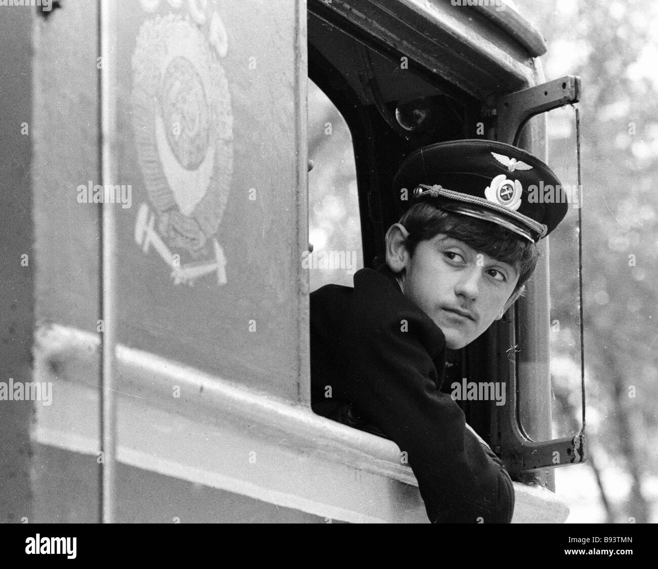 A young locomotive engineer looks out of a locomotive cabin A railway for children in Chkalovsk Park - Stock Image