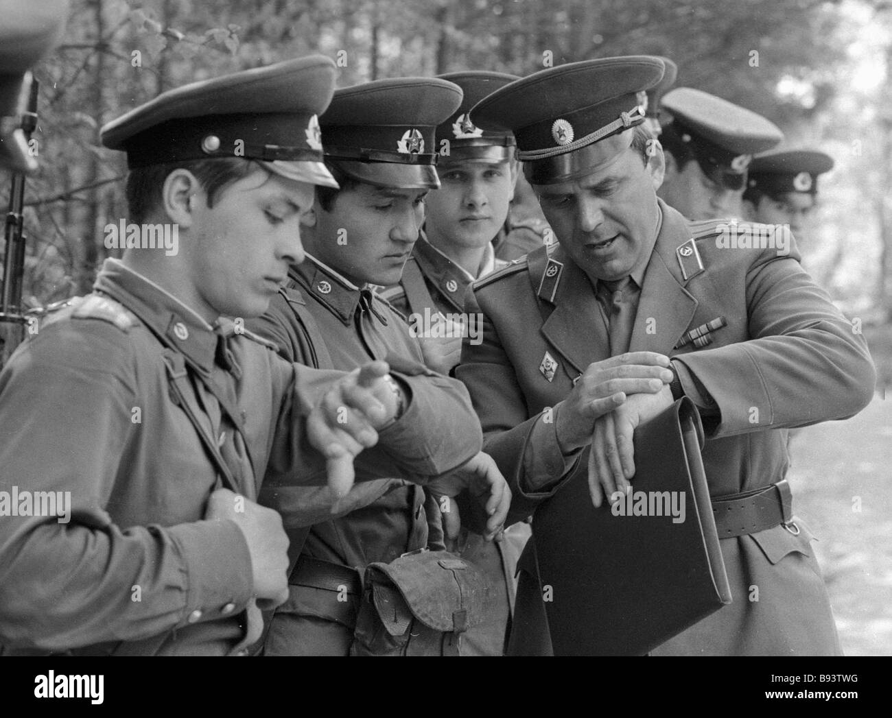 Cadets of the Moscow Mossovet Border Guards Command Higher School of the USSR KGB synchronizing watches before fulfilling - Stock Image