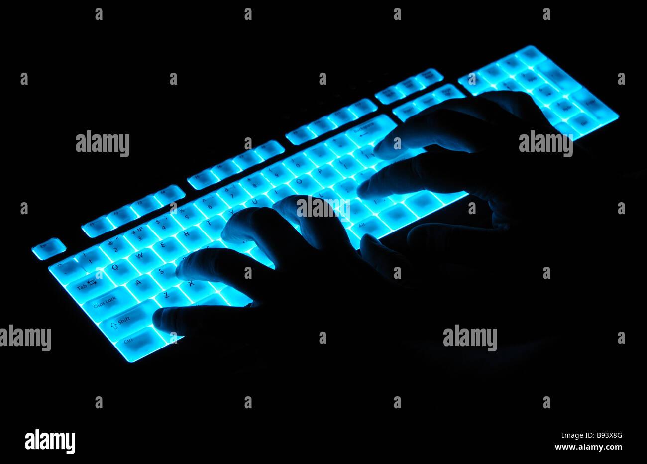 hands over luminous keyboard - Stock Image
