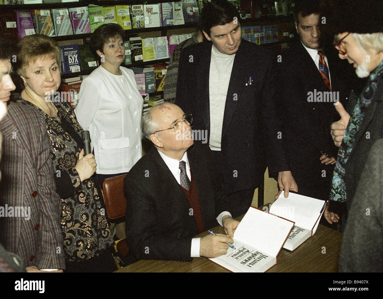 Russia s ex president Mikhail Gorbachev sitting signing for the buyers his book Life and the Reforms during its - Stock Image