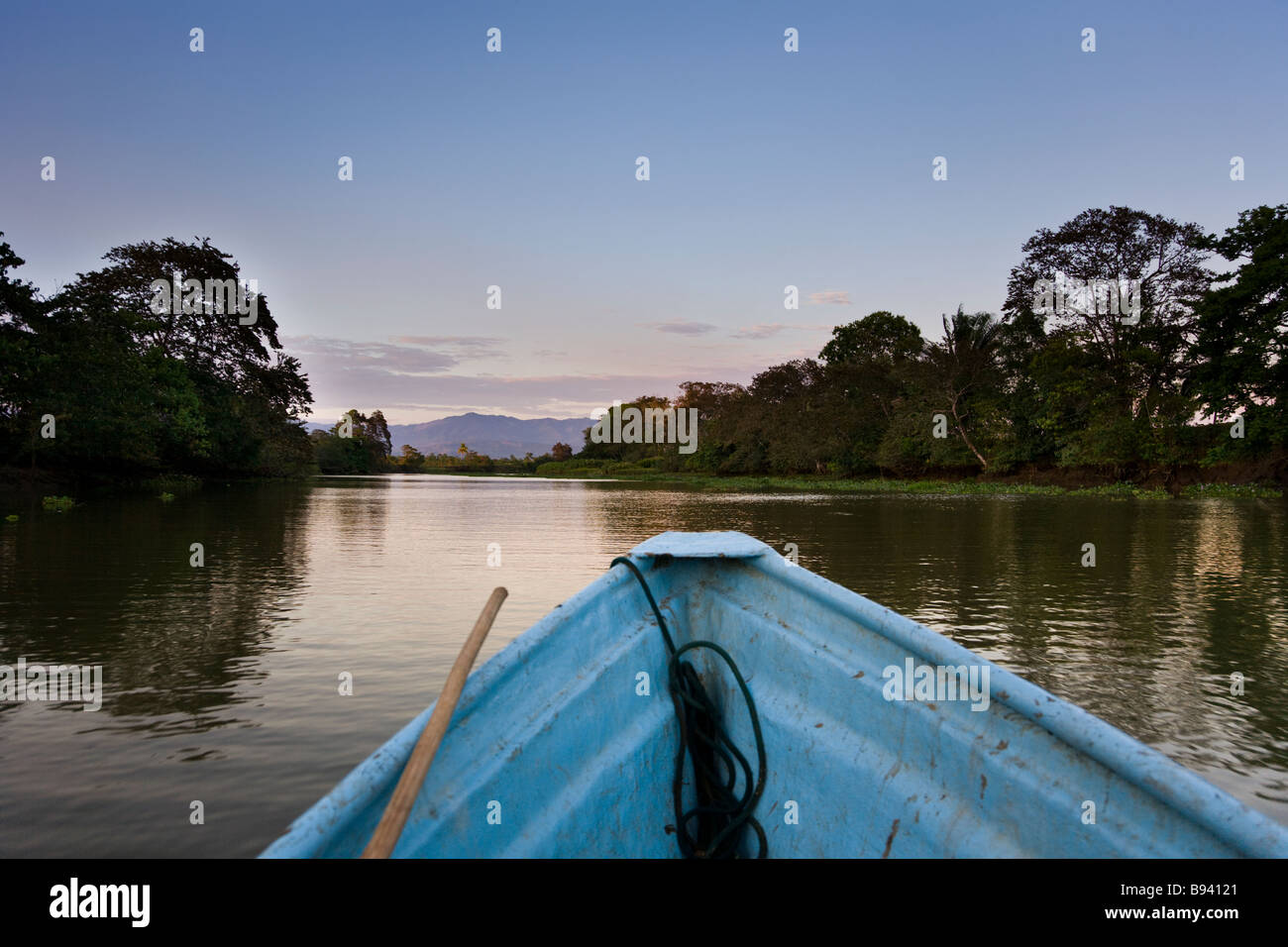 A boat going down the Sierpe River, gateway to Costa Rica's Corcovado National Park, with mountains in the background - Stock Image