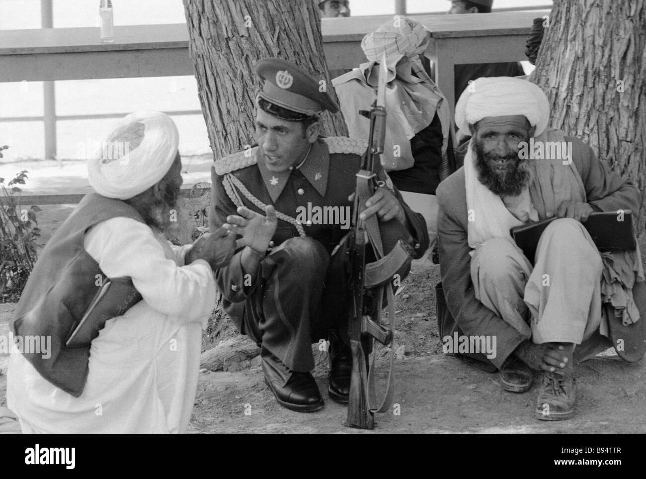 An Afghan soldier talks to the elders of the village - Stock Image