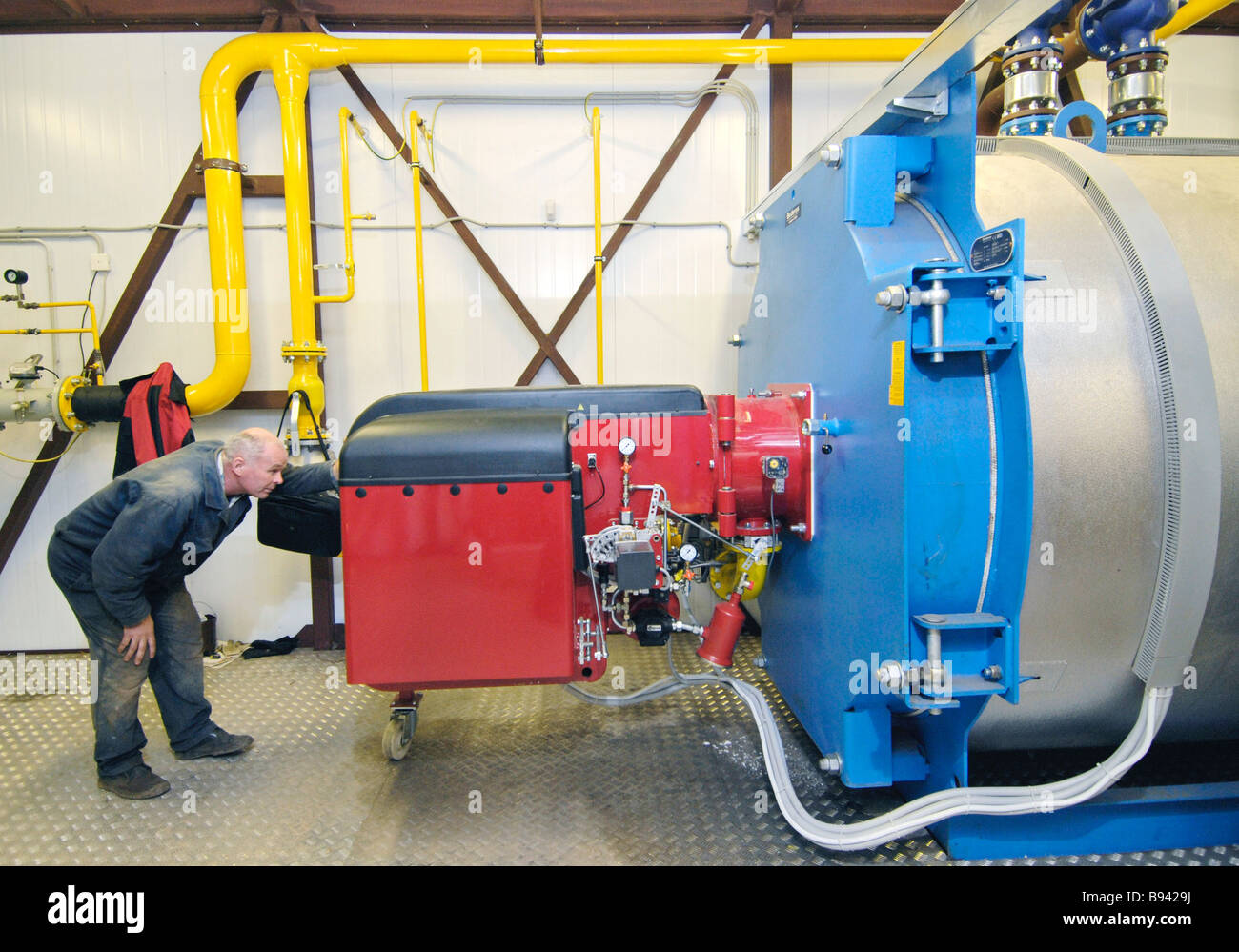 Operating new generation boiler room Expert watches operational water heating boiler - Stock Image