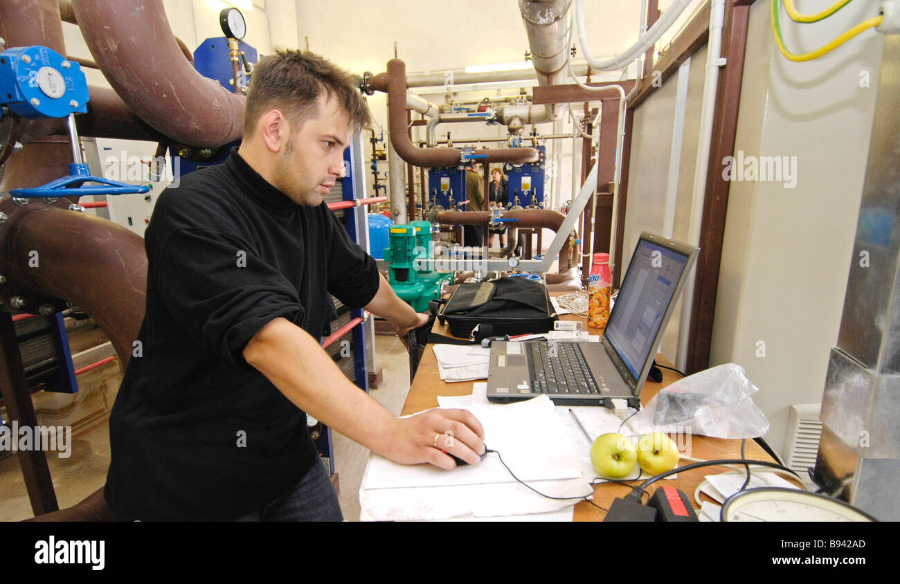 Operating new generation boiler room Operator uses notebook to adjust equipment - Stock Image