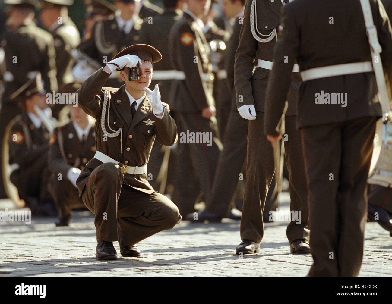 A member of a brass band taking a photo of a military parade dedicated to the 57th anniversary of victory in the - Stock Image
