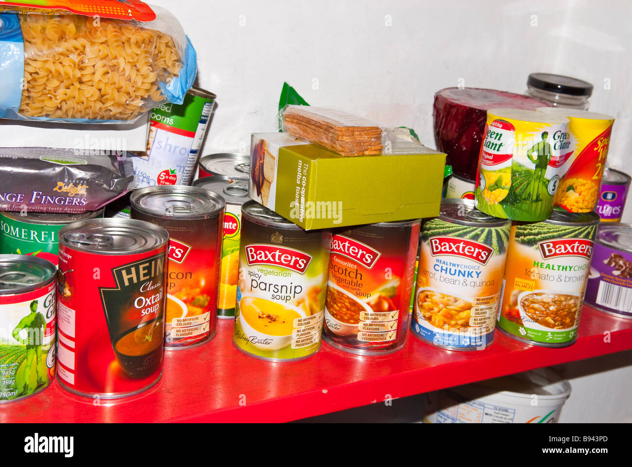 A cluttered untidy larder pantry housing lots of tins of food - Stock Image