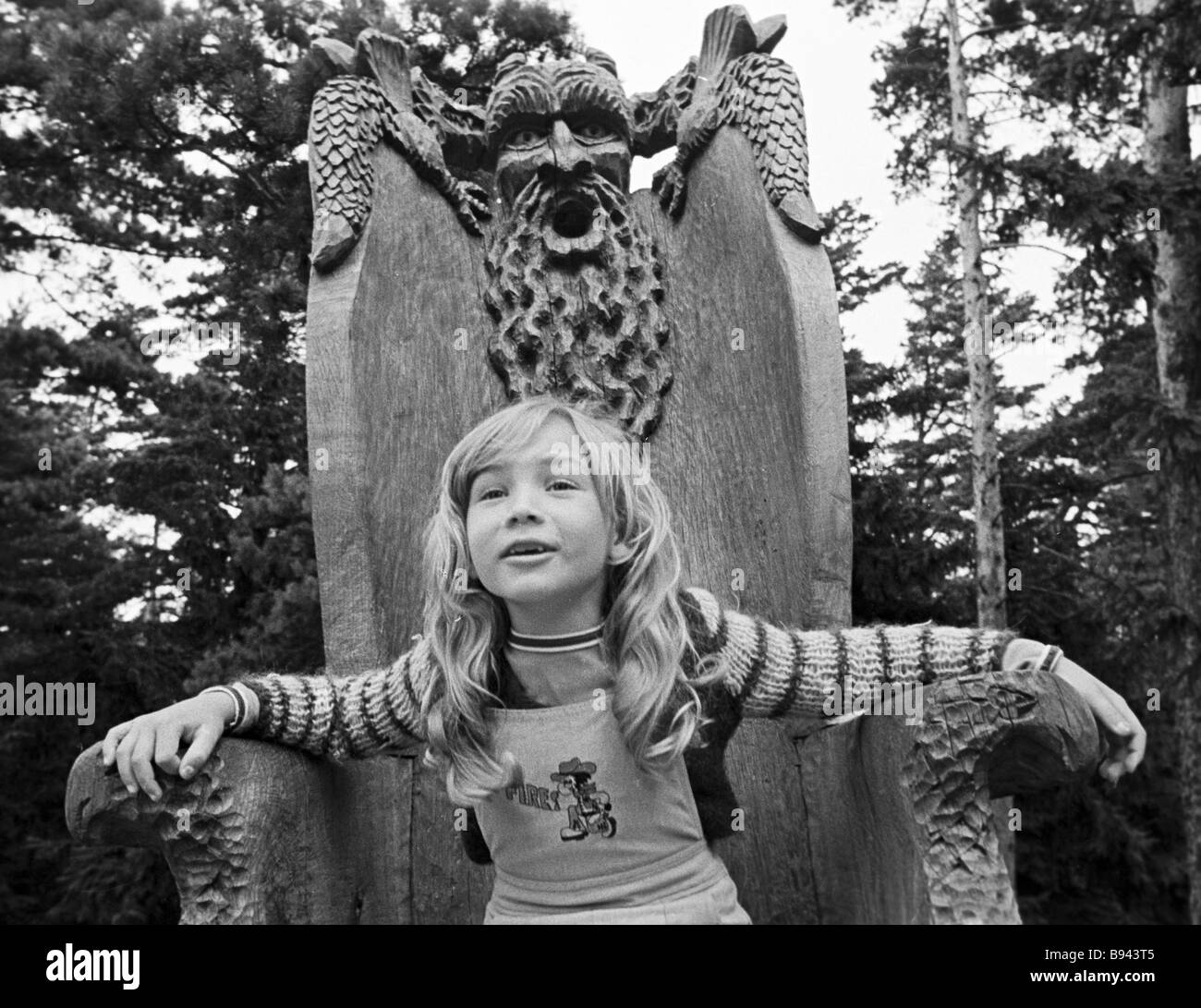 A girl sits in a fancy chair in the park on the Witches mountain where a set of wooden sculptures was created - Stock Image