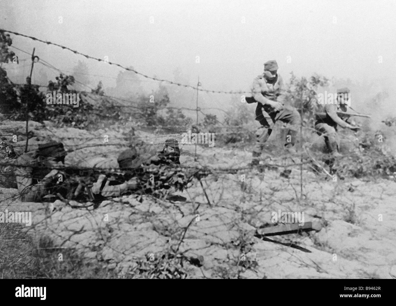 Wojsko Polskie 1st Army troops negotiate an enemy barbed wire entanglement - Stock Image