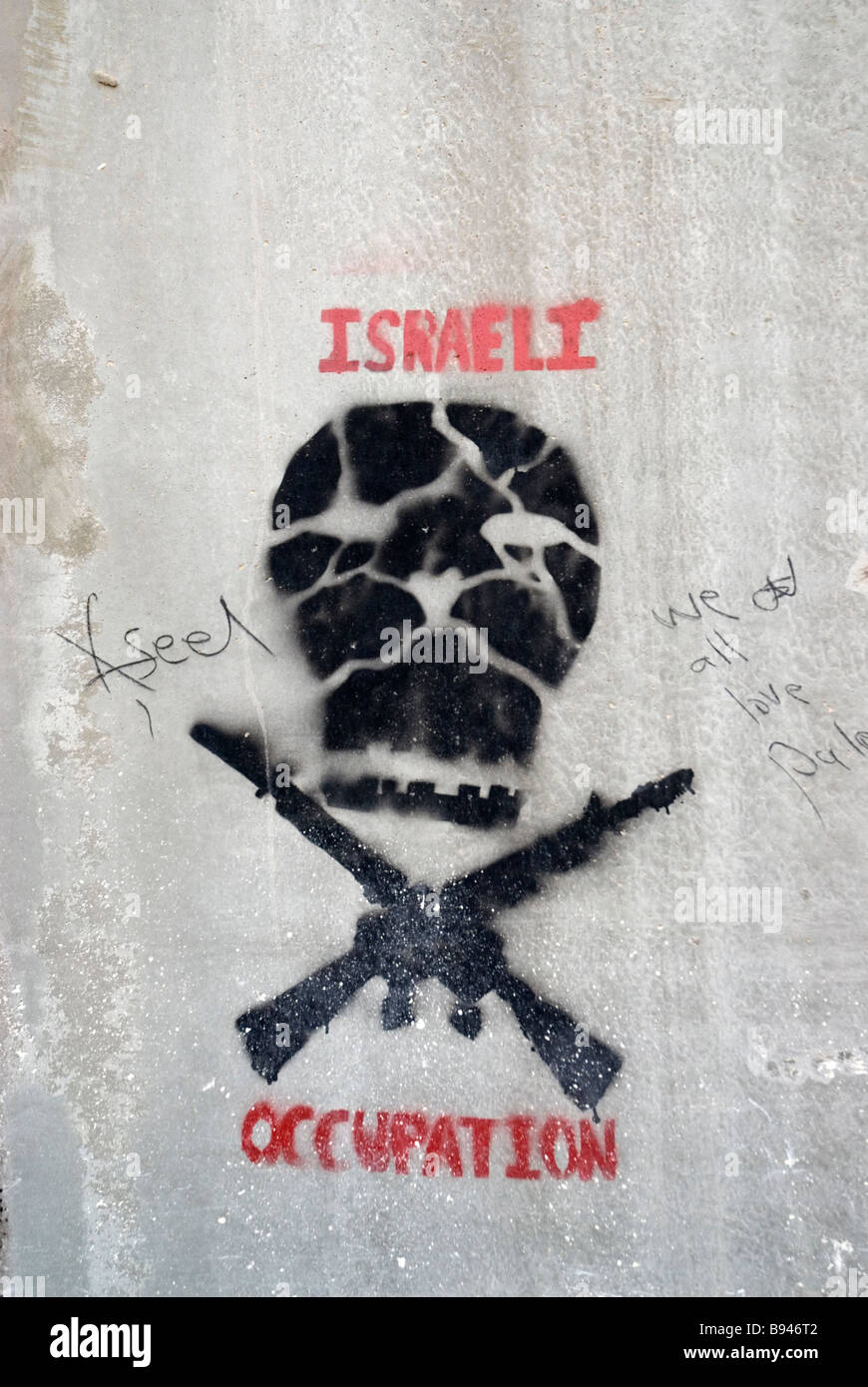 Palestine West Bank . Separation wall. Graffitti of skull and guns and words Israeli Occupation - Stock Image