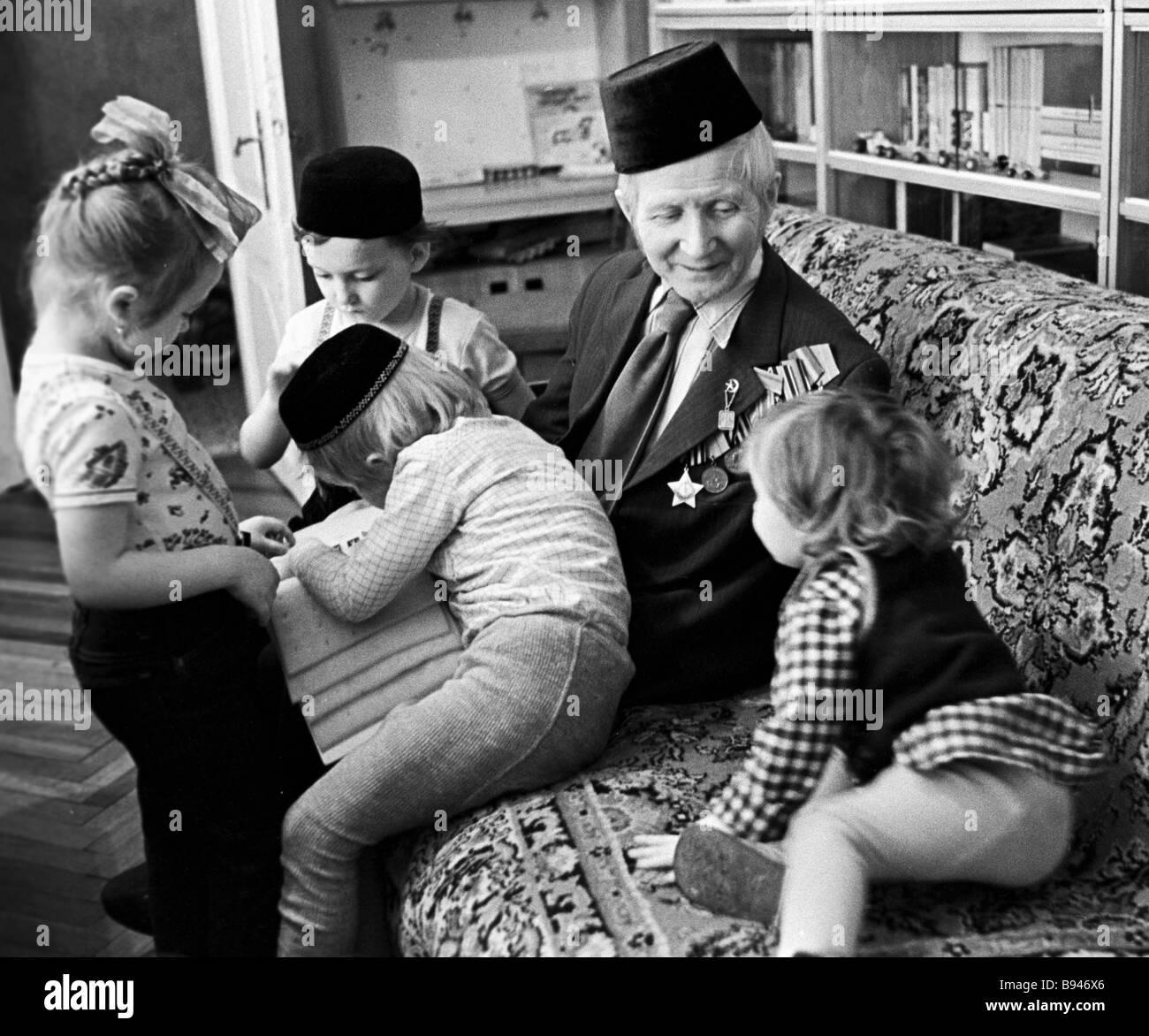 Second World War veteran Osman Brundukov with his grandchildren - Stock Image