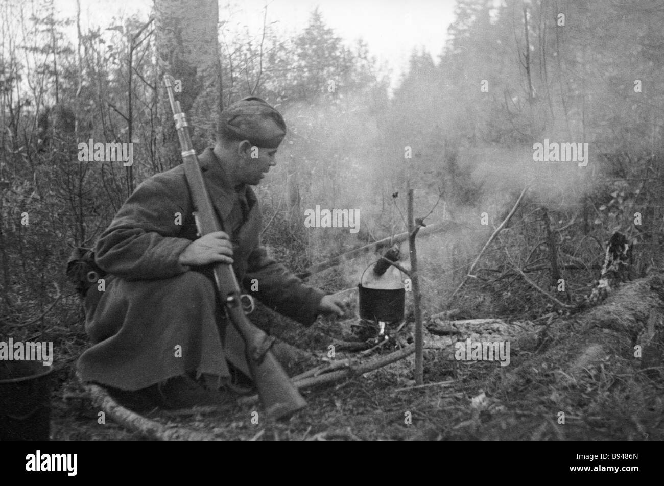 A Soviet troop cooks a meal on a fire on a short forest stop - Stock Image