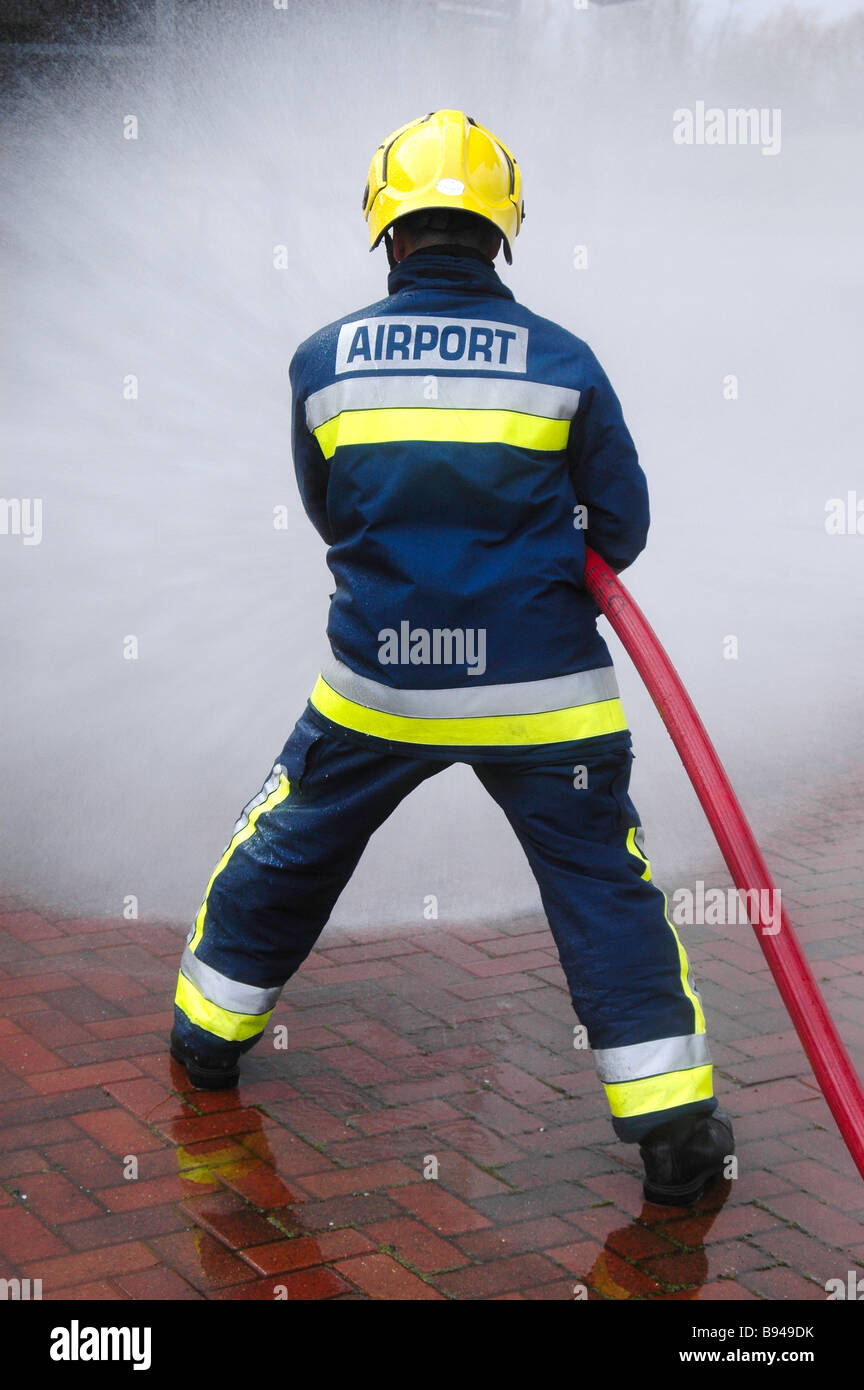 An airport firefighter from behind operating a hose - Stock Image
