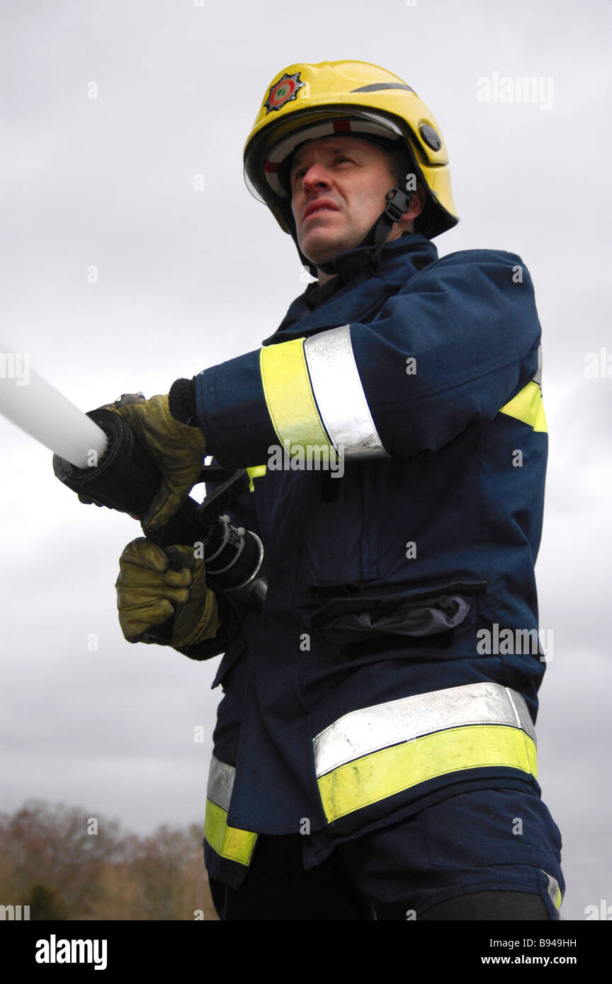 An airport firefighter operating a hose - Stock Image