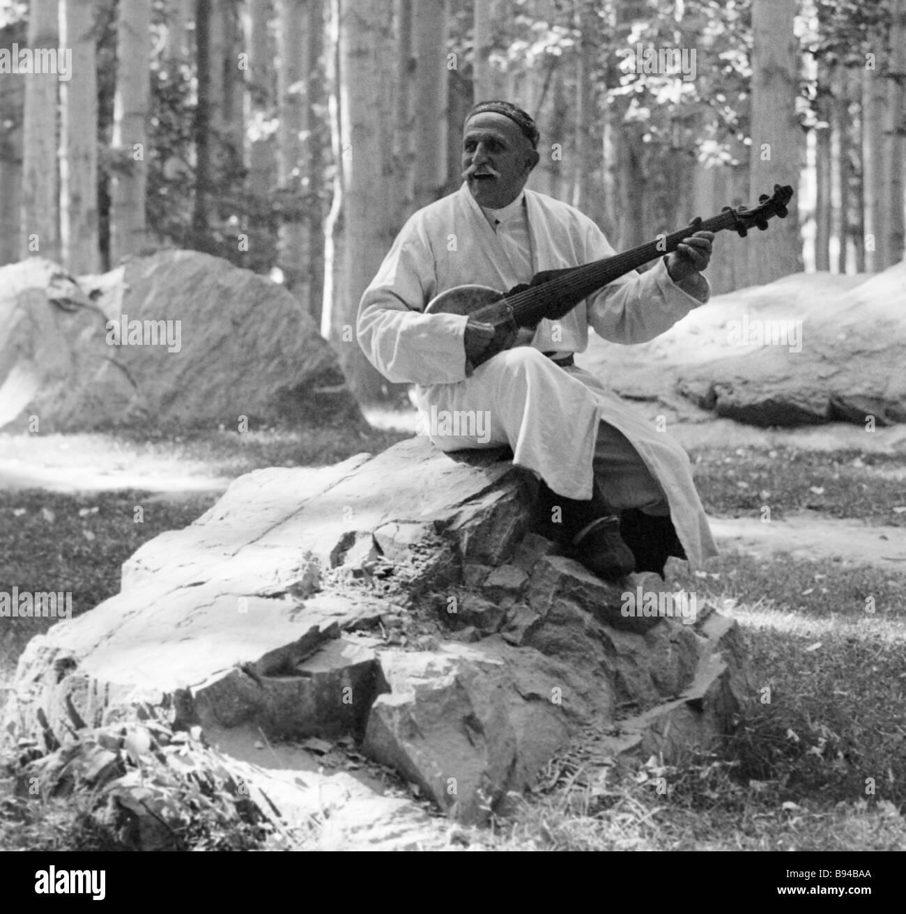 Tajik bard Navruzsho Kurbonaseinov is playing the tambur folk string instrument - Stock Image