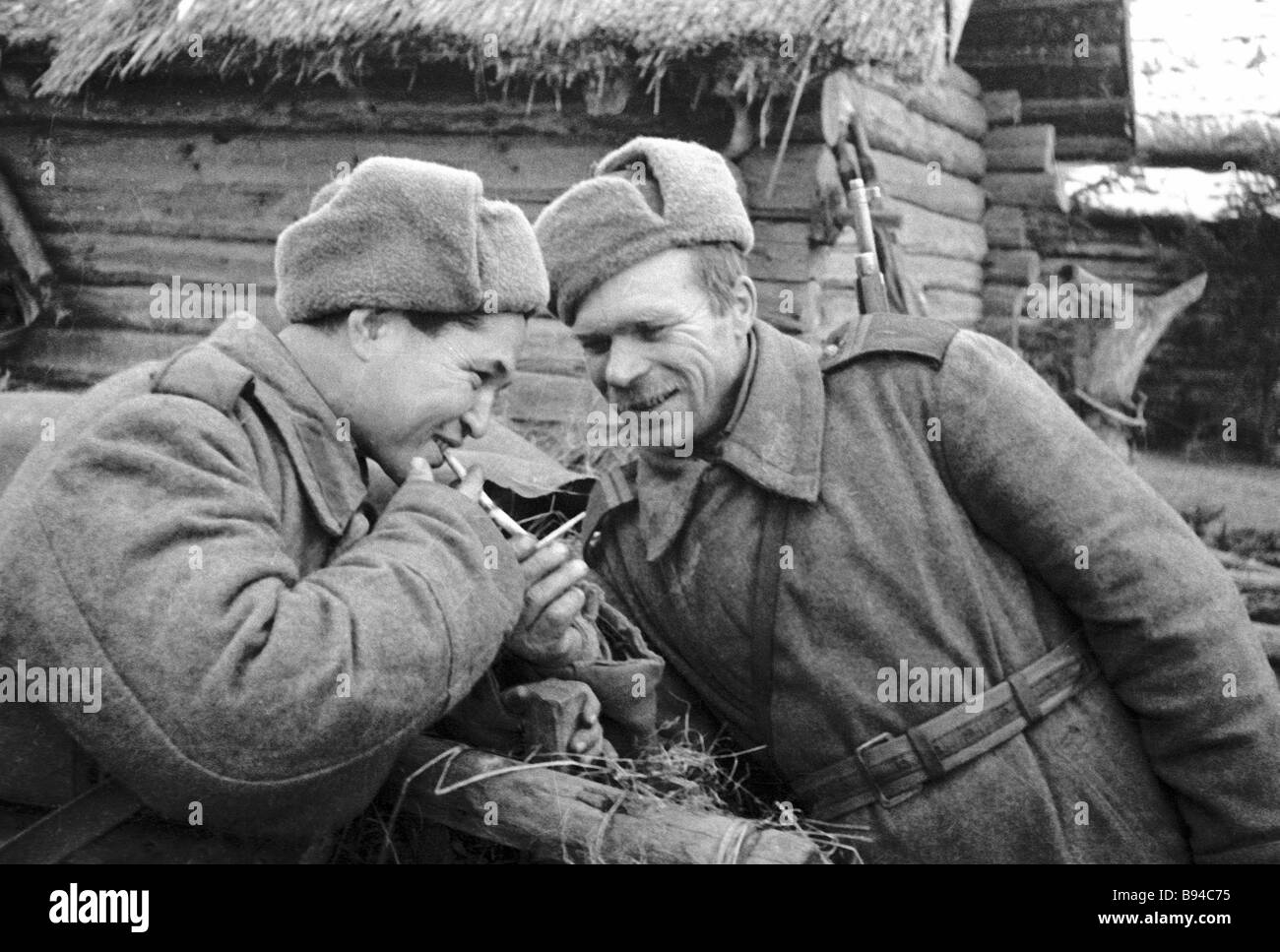 Soviet frontline troops roll their cigarettes - Stock Image