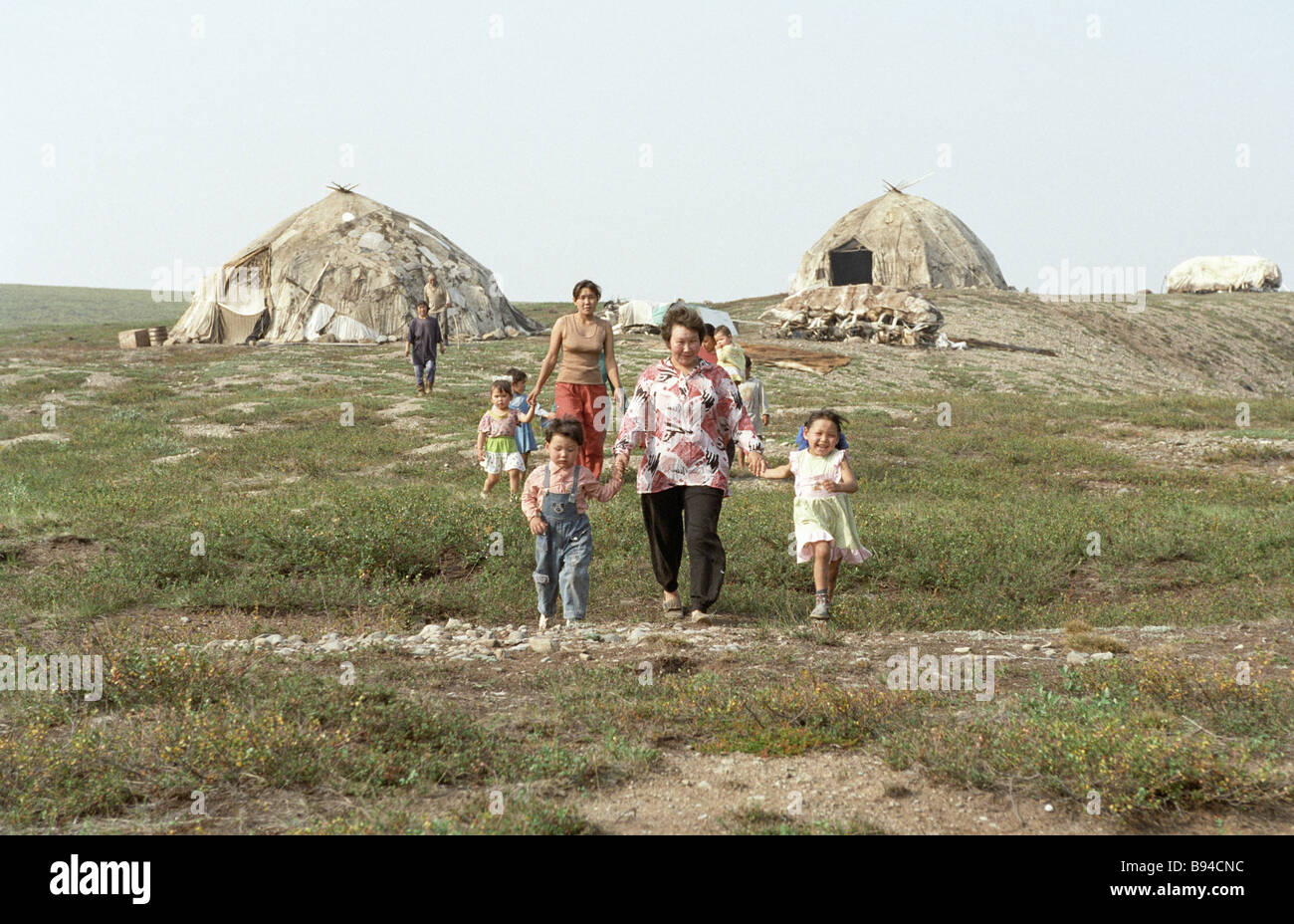 Women and children from the Kanchalan village going to meet a helicopter with visitors - Stock Image