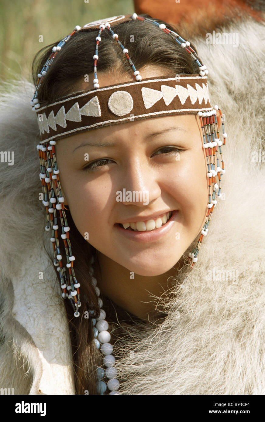 Member of the Chukotka song and dance ensemble wearing a national head dress - Stock Image