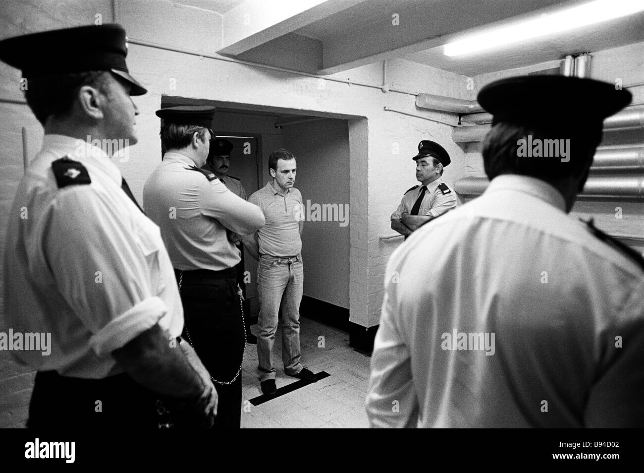 Prison officers watch over a prisoner toeing the line during an interview with the govenor Pentonville Prison London - Stock Image