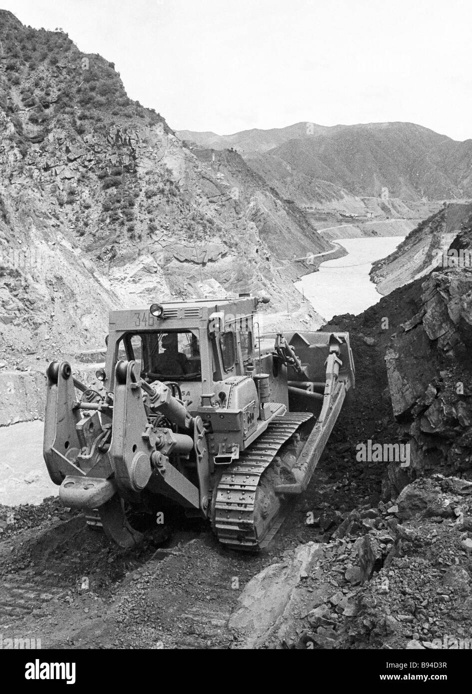 Bulldozer Skalolaz Cliff Hanger expands the Vakhsh River s banks during construction of the Rogun hydro electric - Stock Image