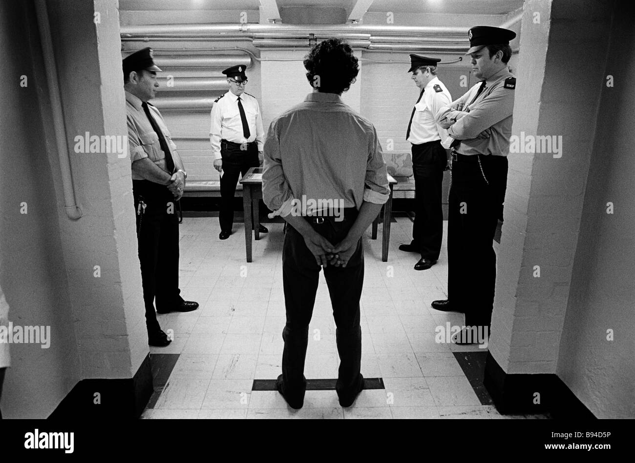 Prison officers watch over a prisoner toeing the line during an interview with the governor Pentonville Prison London - Stock Image