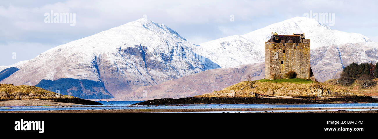 remotely secluded castle Stalker with snow covered mountains in the back and evening sun washing its walls - Stock Image