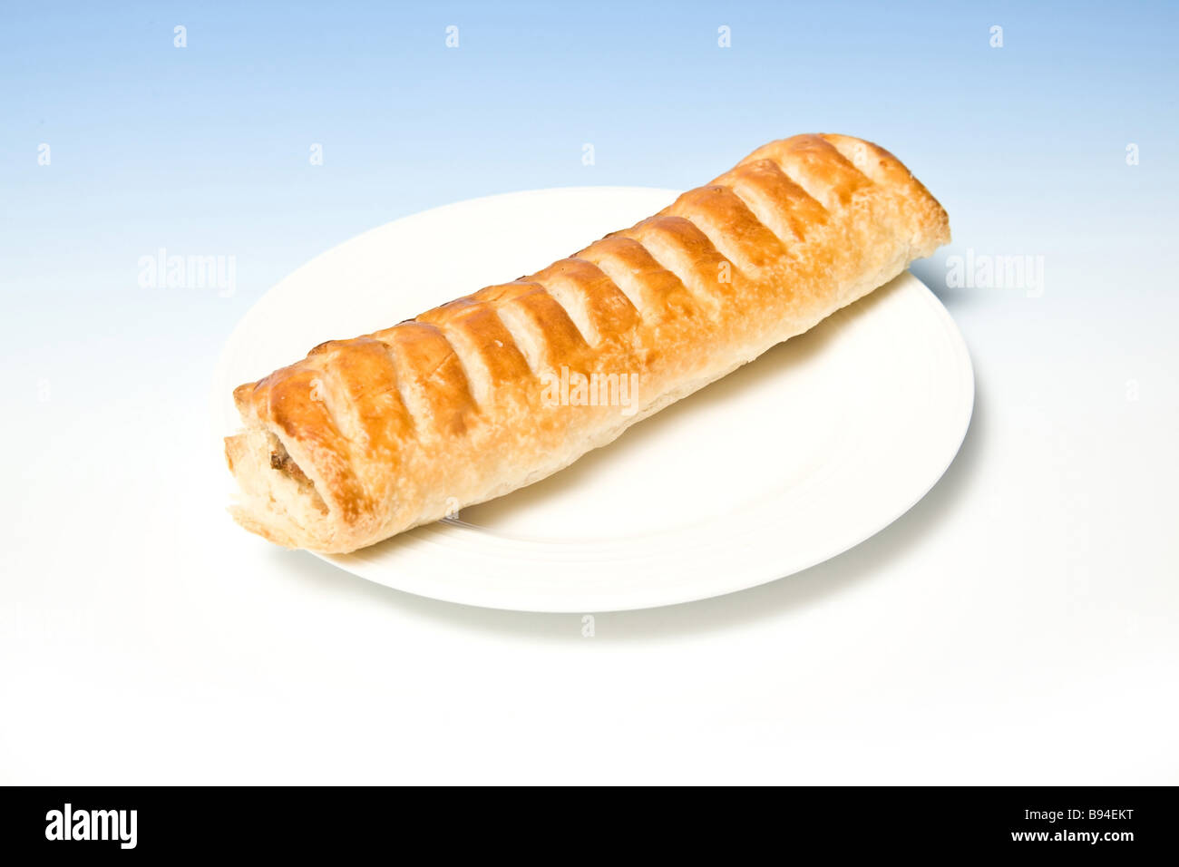Jumbo Sausage roll on a white plate - Stock Image