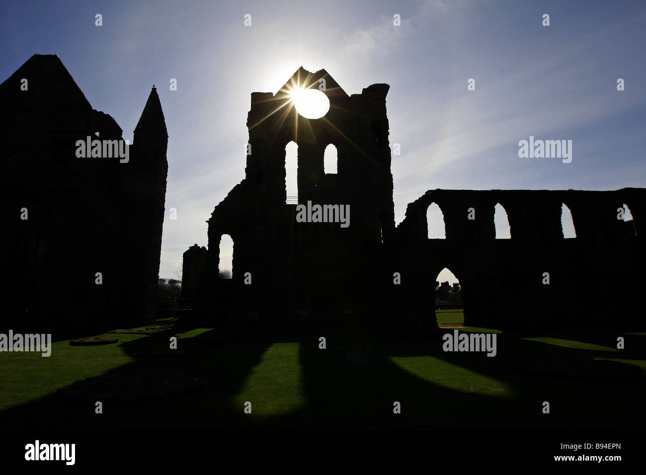 The sun shines through the rose window of the famous and historically important ruins of Arbroath Abbey in Scotland, - Stock Image