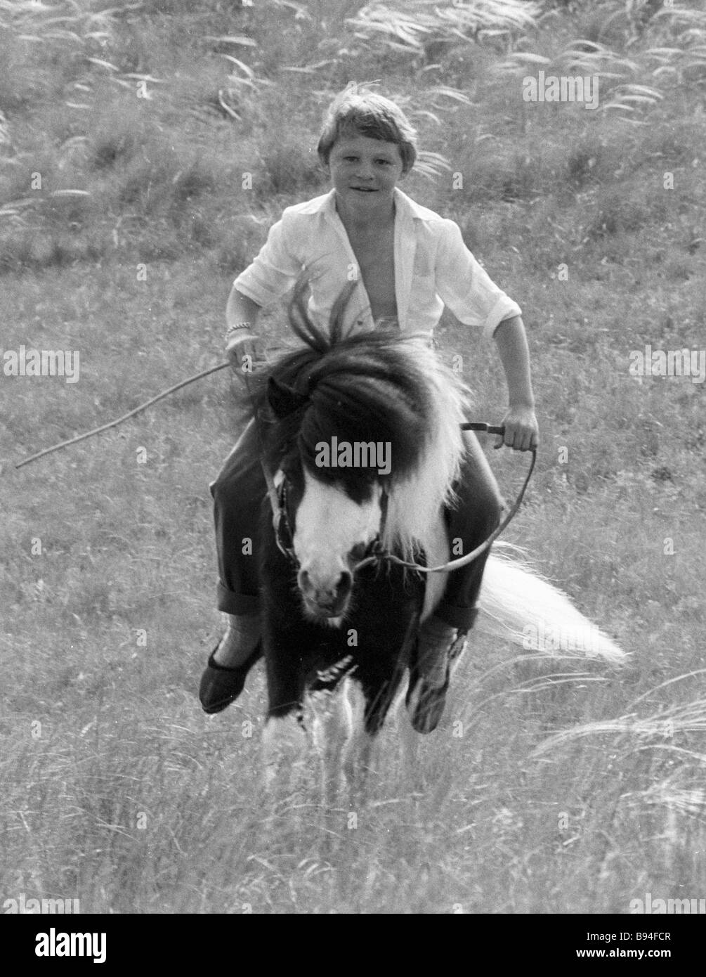 A Bashkir boy breaks in a horse at the Tulpar riding center Stock Photo