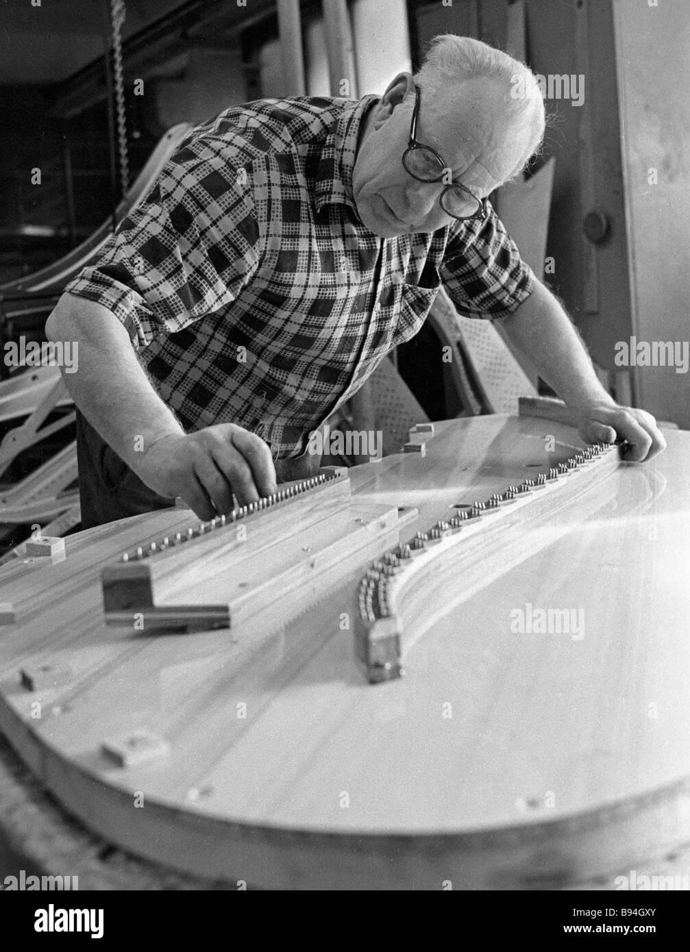 Piano maker Ilo Polakes installing a string palte - Stock Image