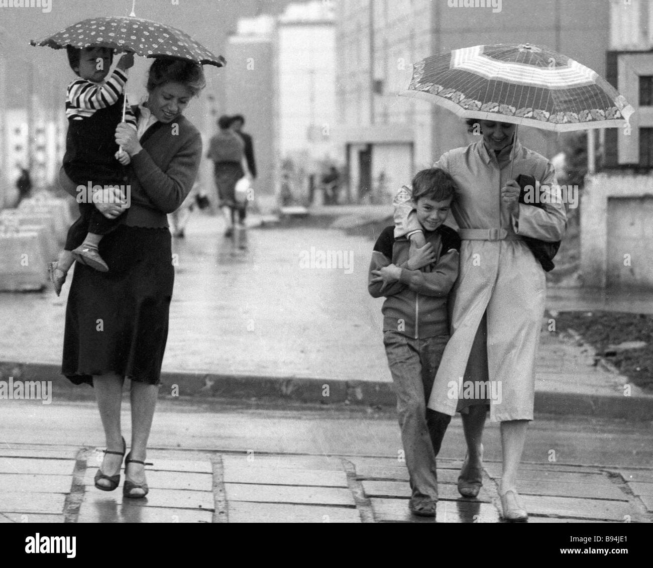 Passers by hide behind umbrellas on a rainy day - Stock Image