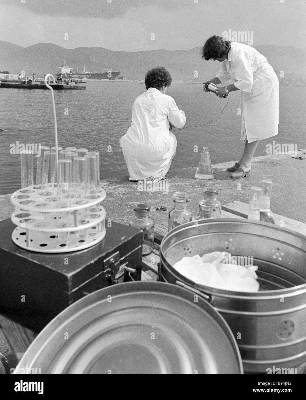 Assistants of the municipal sanitary epidemiological service taking sea water samples on the city beach Stock Photo